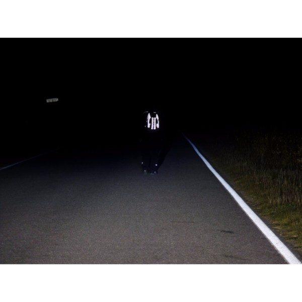 Jalankulkija jolla on Huomio Heijastava Reppu selässään. Näkyy hyvin pimeällä tiellä.