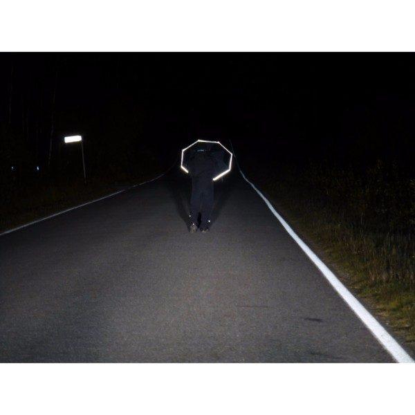 Jalankulkija maantiellä. Hänellä on Huomio Heijastava Sateenvarjo joka näkyy pimeällä tiellä.